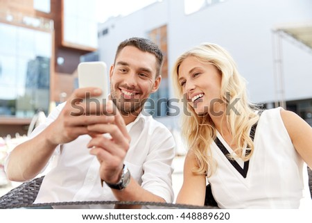 love, date, technology, people and relations concept - smiling happy couple with smatphone at restaurant terrace