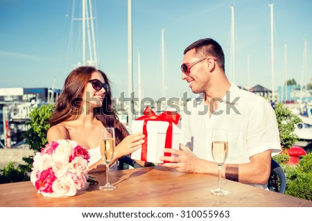 love, dating, people and holidays concept - smiling couple wearing sunglasses sitting with gift box, flowers and champagne at cafe