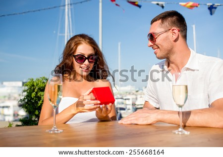 love, dating, people and holidays concept - smiling couple wearing sunglasses with champagne and red gift box looking to each other at cafe - stock photo