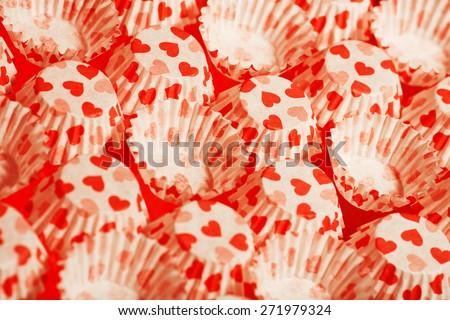 Love desserts concept. Empty paper cases with red hearts for cupcakes over red background. Close up. Studio shot - stock photo