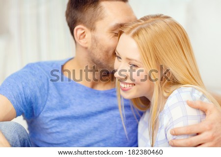 love, family and happiness concept - man kissing young woman at home - stock photo