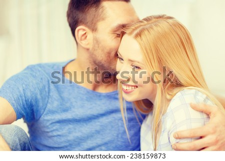 love, family and happiness concept - man kissing young woman at home
