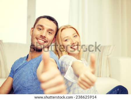 love, family and happiness concept - smiling happy couple at home showing thumbs up - stock photo