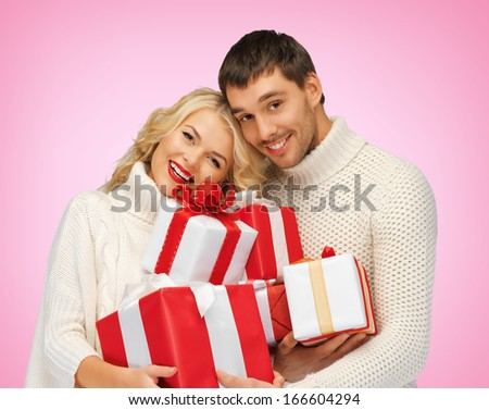 love, family and holidays concept - romantic couple in sweaters with many gift boxes