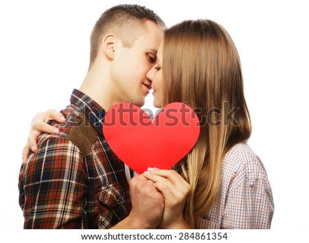 Love, family and people concept: Sweet kiss. Happy couple in love holding red heart.