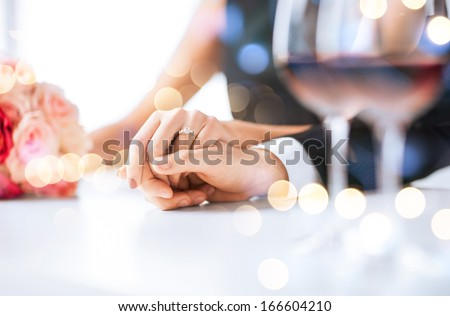 love, family, anniversary concept - engaged couple with wine glasses in restaurant - stock photo