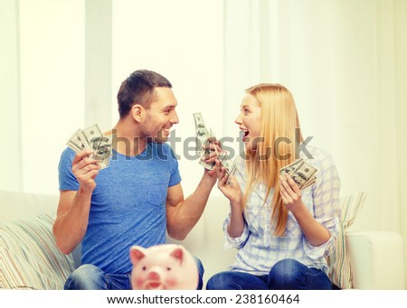 love, family, finance, money and happiness concpet - smiling couple with money and piggybank ot table at home - stock photo