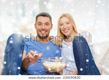 love, family, technology, entertainment and people concept - smiling couple watching tv and lying on sofa at home - stock photo
