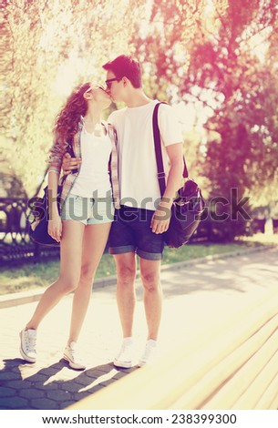 Love, fashion and people concept - summer stylish pretty young couple kissing outdoors in the sunny city park  - stock photo