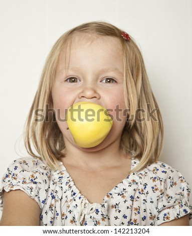 Love for apples - girl biting into the apple - stock photo