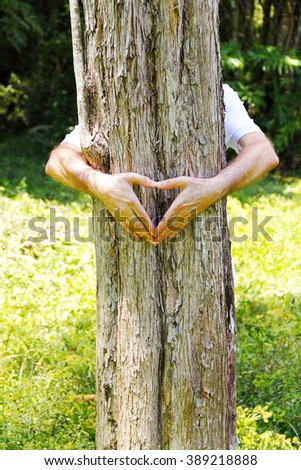 Love For Nature. Hands in heart shape and arms embracing a tree trunk, expressing the need of taking care of the environment and the relationship with a healthy lifestyle.