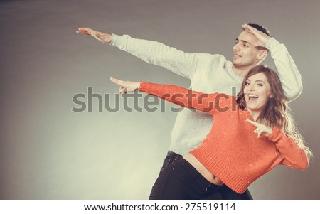 Love friendship and happiness concept. Smiling young couple having fun, happy man and woman studio shot on gray - stock photo
