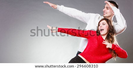 Love friendship and happiness oncept. Smiling young couple having fun, happy man and woman studio shot on gray - stock photo
