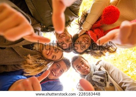 love, friendship, gesture, season and people concept - group of smiling men and women showing thums up in autumn park - stock photo