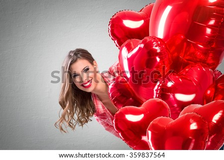 Love girl peeking behind a red balloons, funny Valentine's Day - stock photo