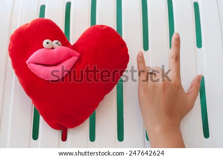 Love hand sign with wedding ring and Love heart doll wink face (White-Green Background) - stock photo