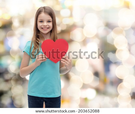 love, happiness and people concept - smiling little girl with red heart - stock photo