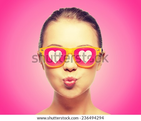 love, happiness, valentines day, face expressions and people concept - portrait of teenage girl in pink sunglasses with hearts blowing kiss - stock photo