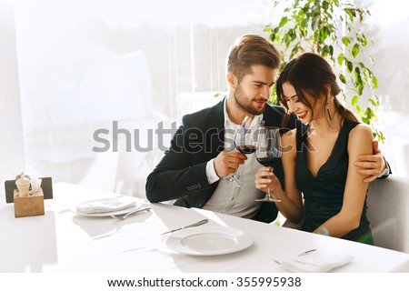 Love. Happy Romantic Smiling Couple Having Dinner, Embracing, Drinking Wine, Celebrating Holiday, Anniversary Or Valentine's Day In Gourmet Restaurant. Romance, Relationships Concept. Celebration - stock photo