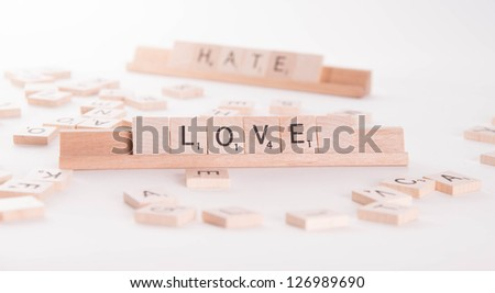 Love Hate concept spelled in Scrabble letters on white background - stock photo