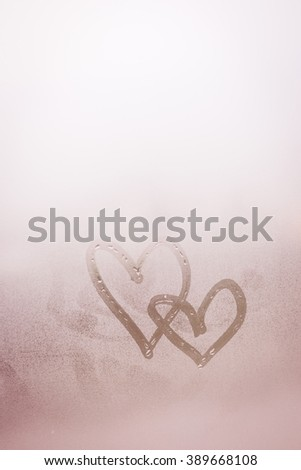 Love heart couple symbol drawn by hand on the wet frozen window glass with sunlight background. Close up - stock photo