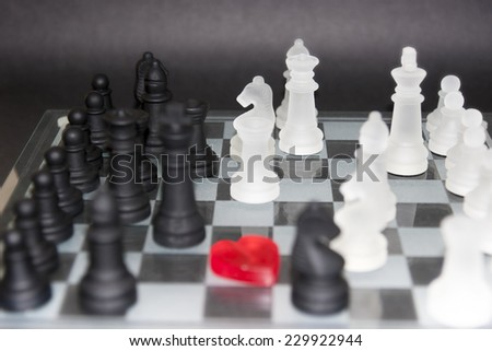 love heart in the centre of a chess board with pieces - stock photo