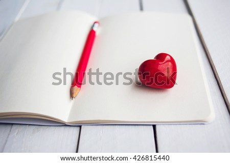 Love heart on notebook with pencil on white wooden table. Place for text. Selective focus. - stock photo