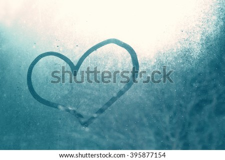 Love heart shape hand drawn on wet, frozen window pane with blue sunlight background. Selective focus used. - stock photo