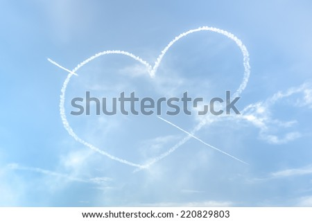 love heart with cupids arrow written in the sky with smoke
