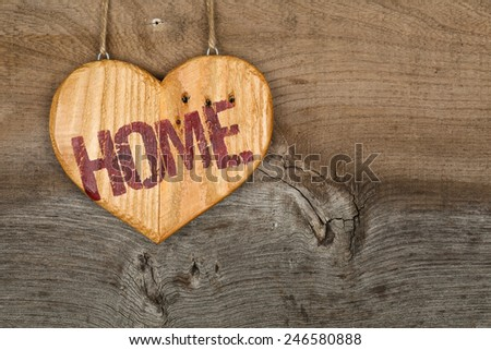 Love Home message wooden heart sign from recycled old palette on rough grey wooden background, copy space