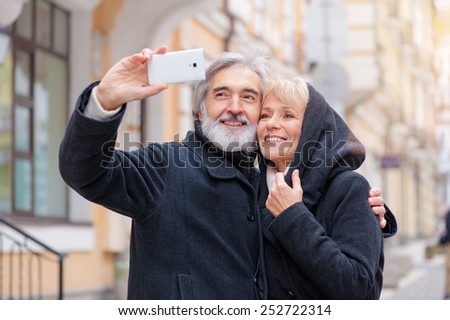 Love in focus. Happy senior caucasian couple bonding to each other and making selfie while standing outdoors - stock photo