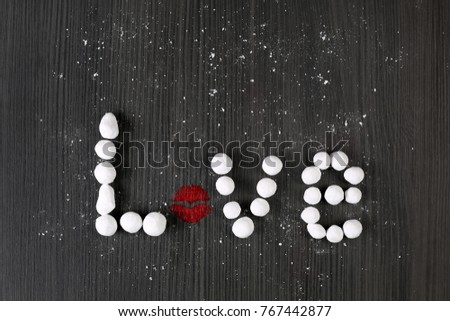 Love inscription is made of sugar white balls and powder with red lipstick lips kiss print on black wooden texture background. Sweet valentine day symbols