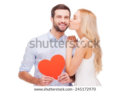 Love is a great feeling! Beautiful young loving couple bonding to each other while woman kissing her boyfriend holding red heart shape paper  - stock photo