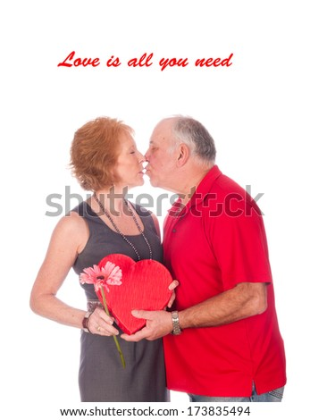 Love is all you need - an elderly couple embracing after the husband gave the wife flowers and chocolates - stock photo