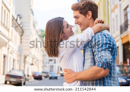 Love is in the air. Beautiful young loving couple hugging and looking at each other while standing outdoors - stock photo