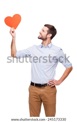 Love is in the air. Handsome young man holding heart shaped valentine card and looking at it with smile while standing isolated on white background   - stock photo