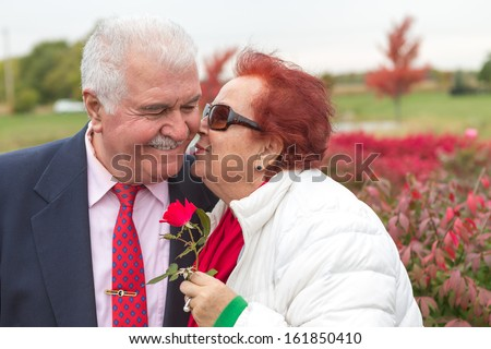 Love is in the air, perhaps she just received the rose from her husband and giving the return kiss - stock photo