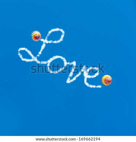 Love is in the air. Two hot air balloons in blue sky and Love word with cloudy text effect. - stock photo