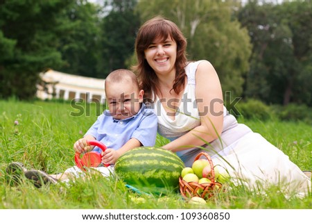 Love laughing family having picnic in summer park against blurred background of green nature