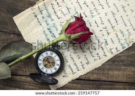 Love letter and rose on wooden background, from above