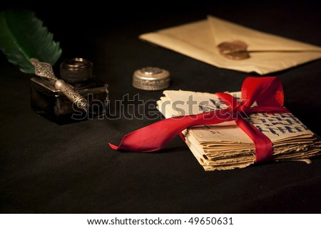 Love letter, antique quill and black ink and stack of letters tied with a red ribbon.