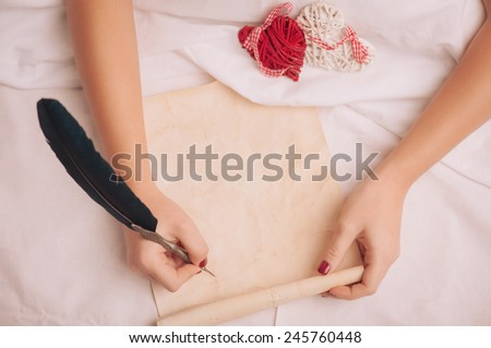 Love letter. Closeup image of woman writing a vintage letter with copy space to valentines day with feather pen while lying in bed - stock photo