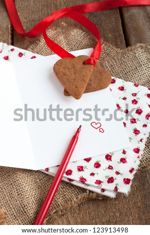 Love letter with heart shape cookies, hearts and red felt pen in rustic style
