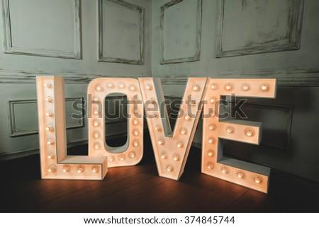 LOVE letter with light bulb in the corner of vintage dark room - stock photo