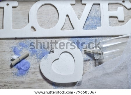 Love letters and glass bottles, small roll paper Put on a wooden background There is a sandy blue sand and one heart.