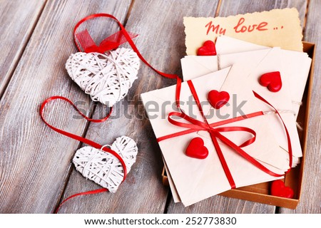 Love letters and hearts on wooden background