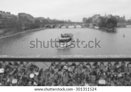 Love locks bridge in Paris. Blurred photo. Black and white. - stock photo