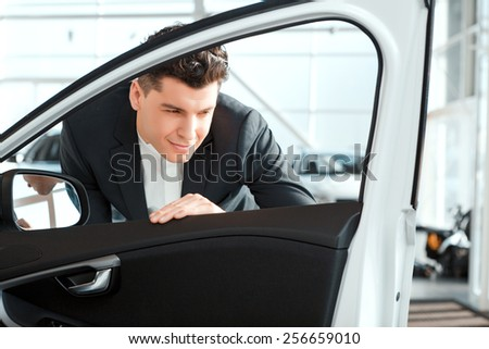 Love luxury cars. Smiling handsome man in formalwear looking inside the new car in car dealership - stock photo