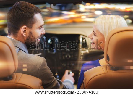 love, luxury, nightlife, automobile  and people concept - happy couple driving in cabriolet car over night city lights background  - stock photo