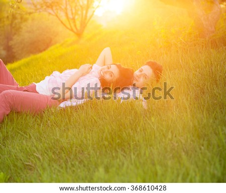 Love. Man and woman couple. Sunset, city park, outdoor - love concept. Spring love story. Couple lovers lying on the green grass in the evening. - stock photo